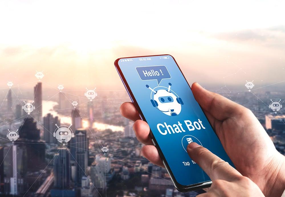 Plano detalles de una mano manipulando un teléfono móvil con un chatbot en pantalla y de fondo el skyline de una ciudad
