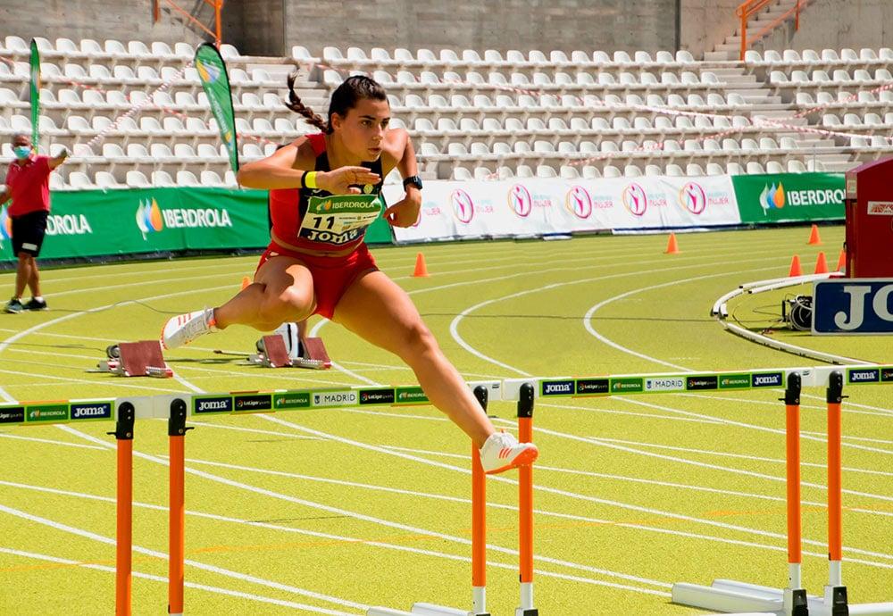 Beatriz Torre salta una valla durante una prueba de atletismo.