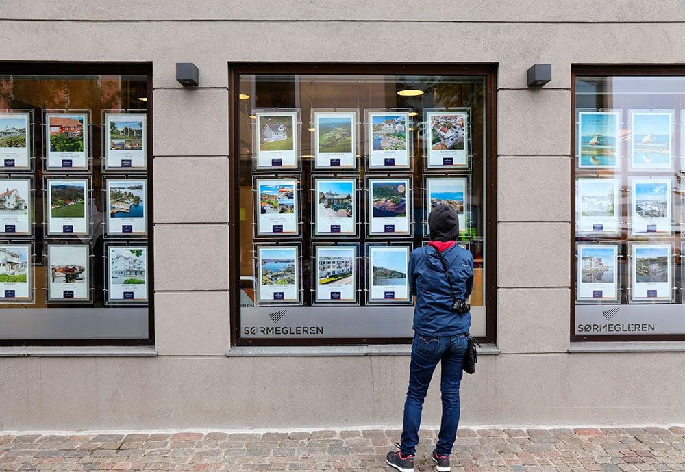 Un hombre de espaldas contempla el escaparate de una inmobiliaria.
