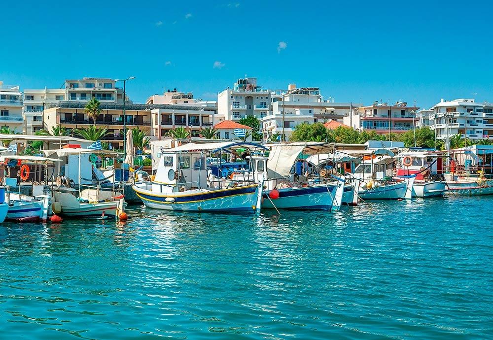 Vista del puerto de Rethymno desde el lado del mar con barcos pesqueros y edificios.