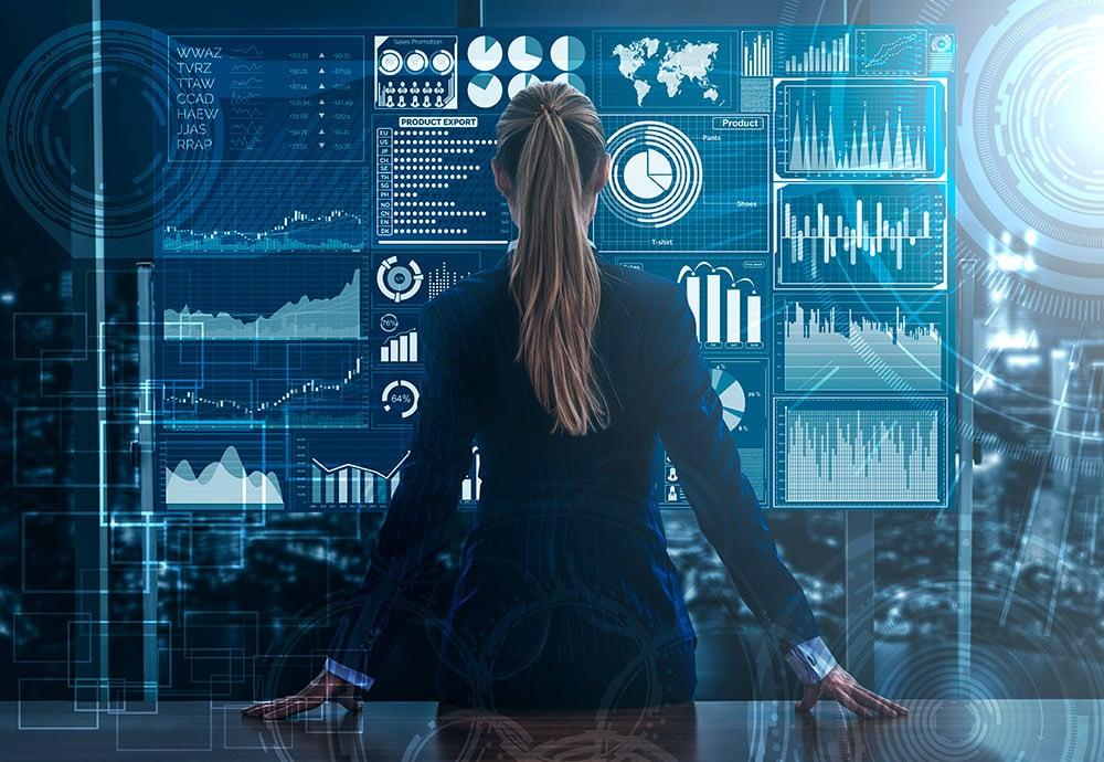 Una mujer observa una pantalla digital con datos y gráficos económicos extraído con tecnología Big data