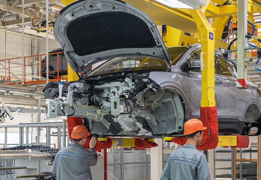 Dos operarios trabajan en una cadena de montajes de coches.