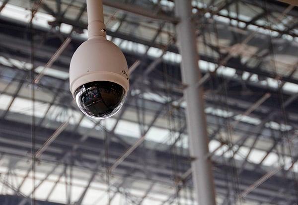 Cámara de videovigilancia colgada del techo de una instalación con cubierta metálica