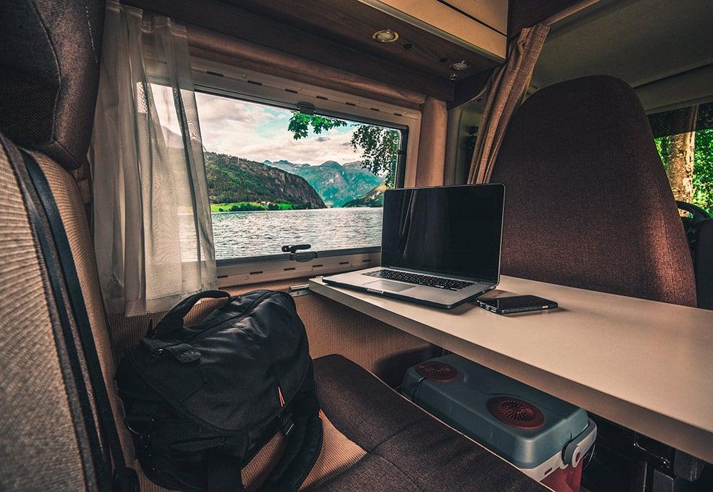 Interior de una autocaravana en la que se muestra una mesa y un portátil encima. A través de la ventana se muestra un lago y un paisaje montañoso.