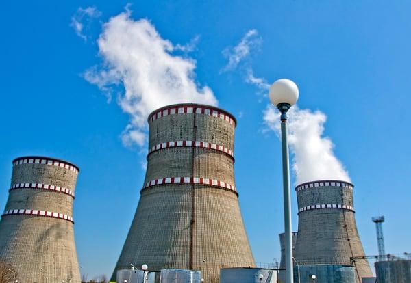 Tres chimeneas de una central nuclear sobre cielo azul emitiendo vapor de agua