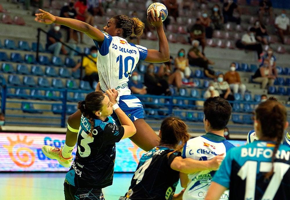 La jugadora del Balonmano Aula Danila So Delgado saltando por encima de jugadoras del equipo rival en el momento justo antes de lanzar a portería.
