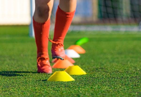 Piernas de un futbolista sorteando unos conos de colores en el césped de un campo de fútbol.