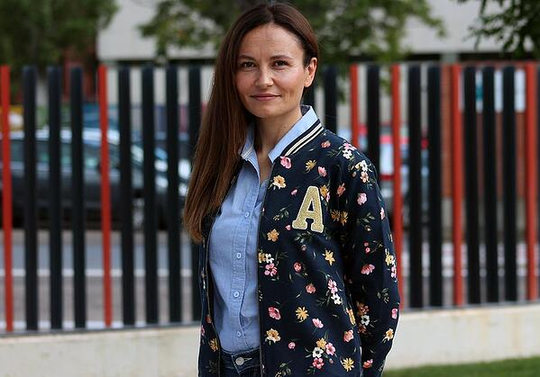 Sonia Garrote con chaqueta azul y estampado de flores delante de una de las vallas de la UEMC