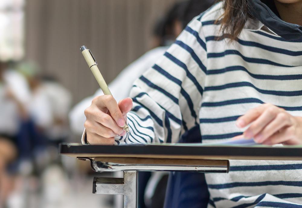 Una chica joven con sudadera de rayas realiza los exámenes de la EBAU