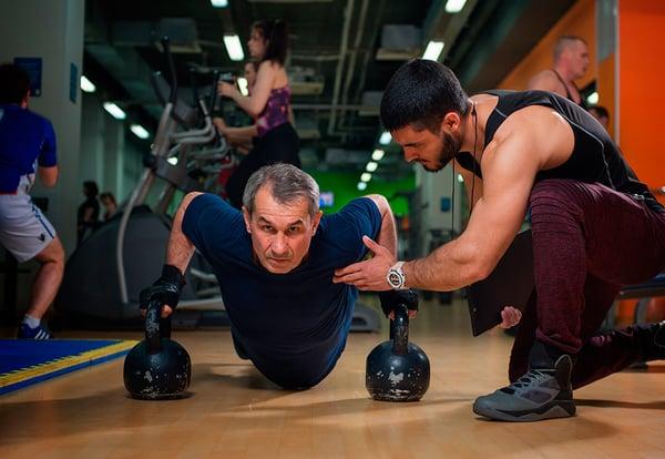 Un hombre mayor realiza un ejercicio en el suelo de un gimnasio siguiendo las directrices de un especialista en poblaciones mayores.