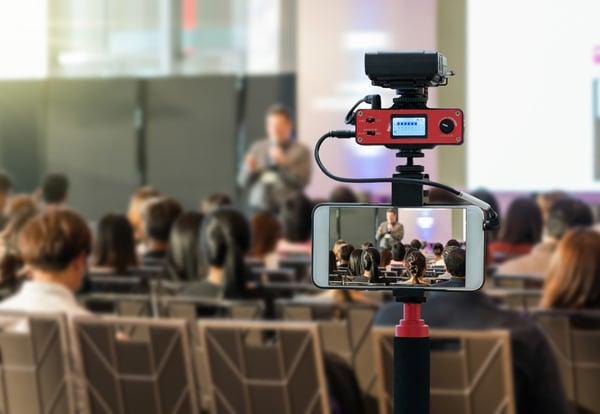 Un teléfono móvil equipado sobre un trípode graba una conferencia en directo