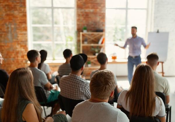 Un grupo de jóvenes escuchan atentamente a un ponente durante una clase