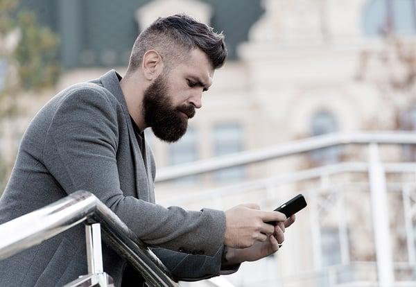 Un hombre joven apoyado en la barandilla maneja su teléfono móvil
