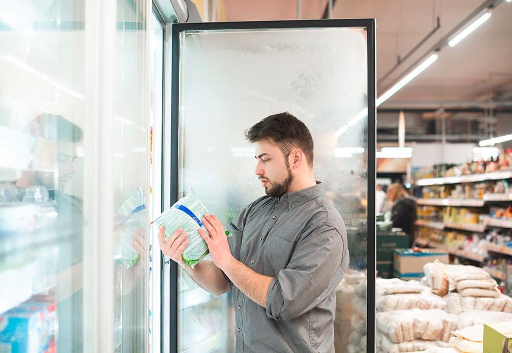 Un hombre con camisa gris sostiene un alimento congelado en el pasillo de un supermercado.