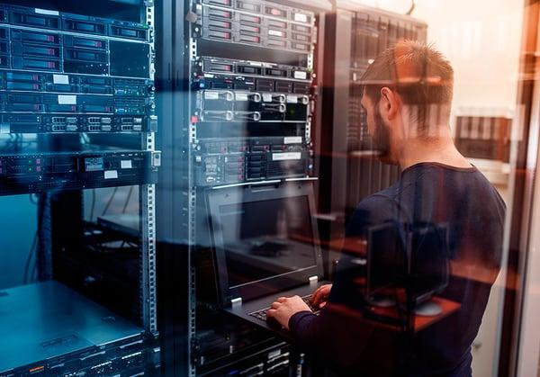 Un estudiante del grado en Ingeniería Informática controlando una terminal en una sala de servidores
