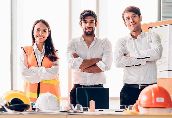 Tres ingenieros de organización industrial, dos chicos y una chica con brazos cruzados mirando a la cámara y unos cascos sobre la mesa