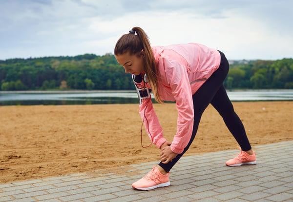 Una corredora joven con chubasquero rosa realiza unos estiramientos en una playa