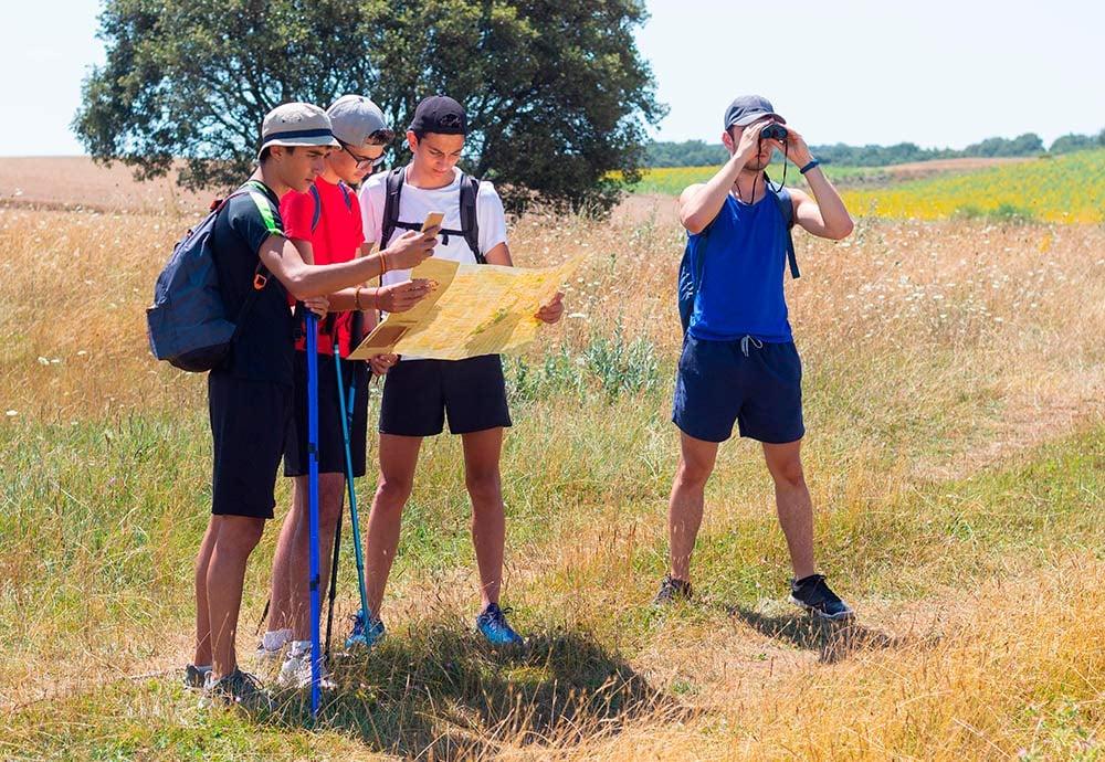 Un grupo de jóvenes consultan un mapa durante una marcha por el campo.