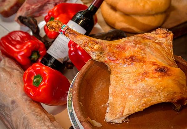 Lechazo en cazuela de barro junto a una botella de vino, pan y pimientos  en el restaurante La Parrilla de San Lorenzo