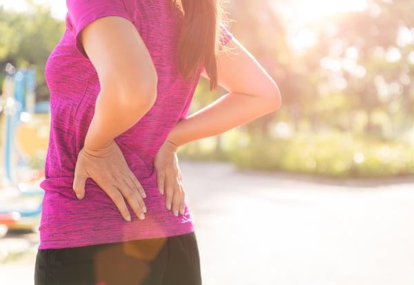 Una mujer se toca la cadera después de haber estado corriendo.