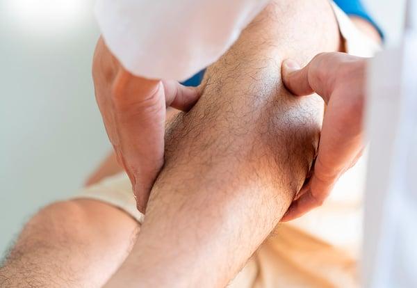 Manos de un fisioterapeuta haciendo una intervención en la pierna de un paciente