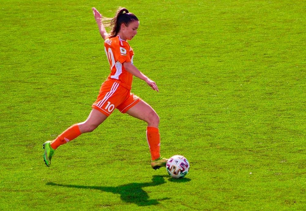 Marta Charle con equipación naranja sube el balón durante un partido de fútbol.