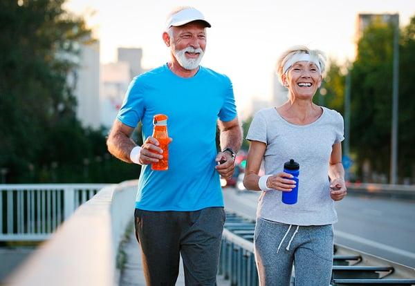 Un hombre uy una mujer mayores practican running por la calle