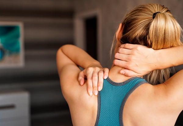 Una mujer joven y deportista se agarra el cuello y el hombre tras sufrir una lesión haciendo ejercicio