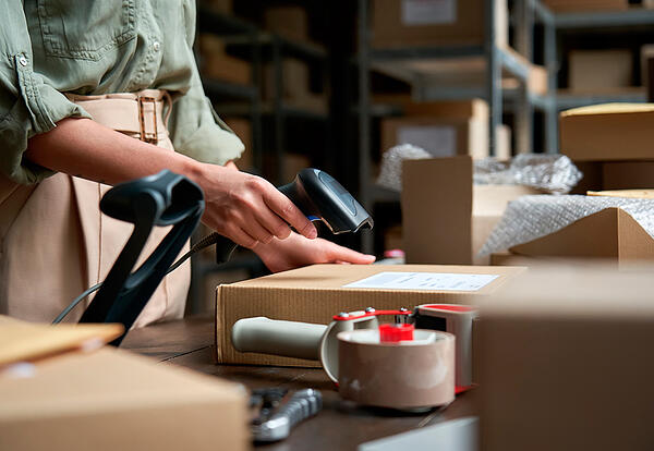 Una mujer escanea la etiqueta de una caja antes de realizar un envío