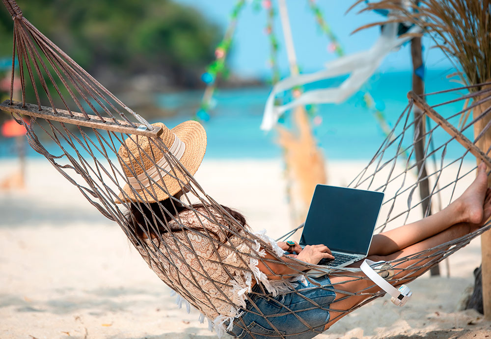 Una mujer teletrabaja con su portátil en una hamaca frente al mar.