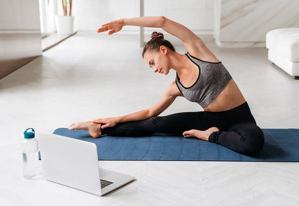 Una mujer practica ejercicio en su casa delante de un PC portátil