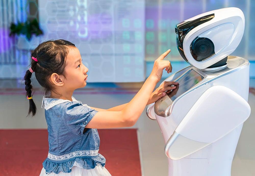 Una niña asiática manipula con su mano la pantalla táctil de un robot