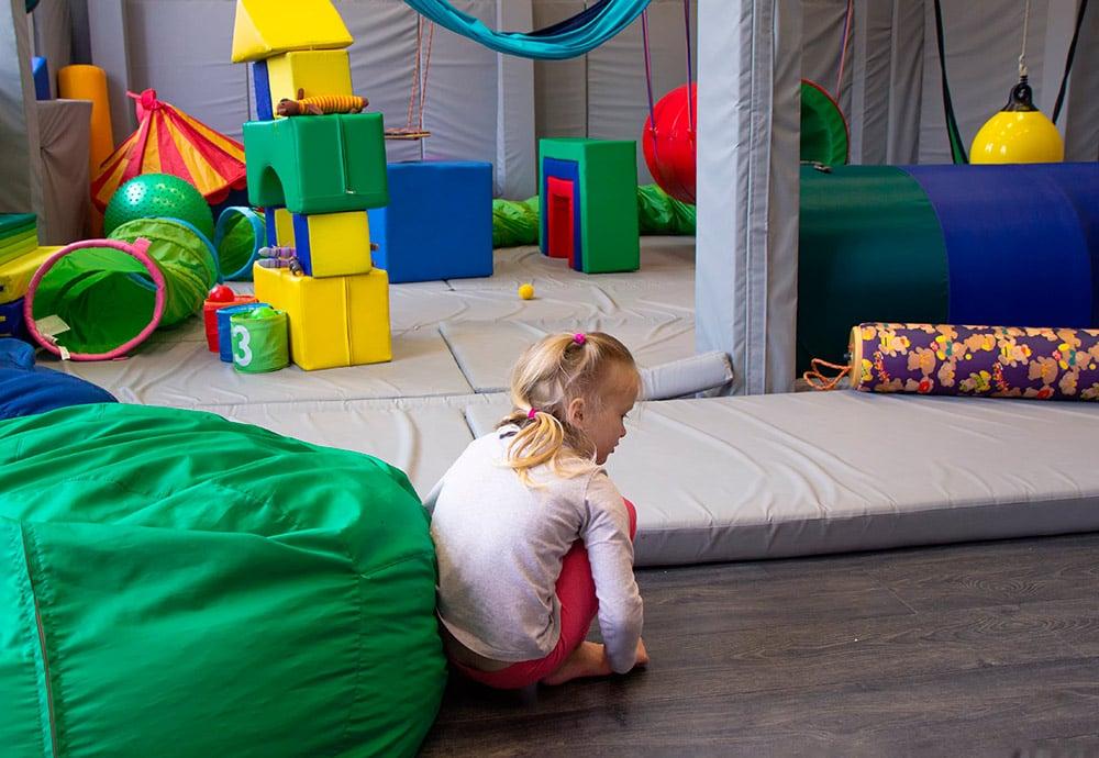 Una niña de cuclillas en el centro de una sala de integración sensorial con colchonetas, columpios y juguetes.