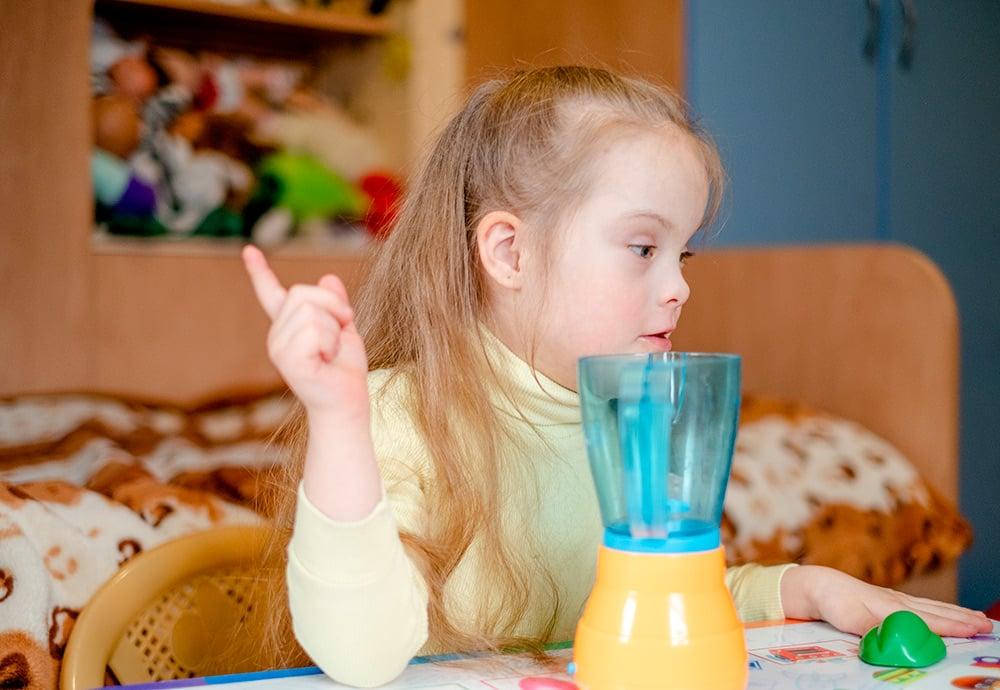 Un niña con síndrome de Down juega con una batidora de juguete.