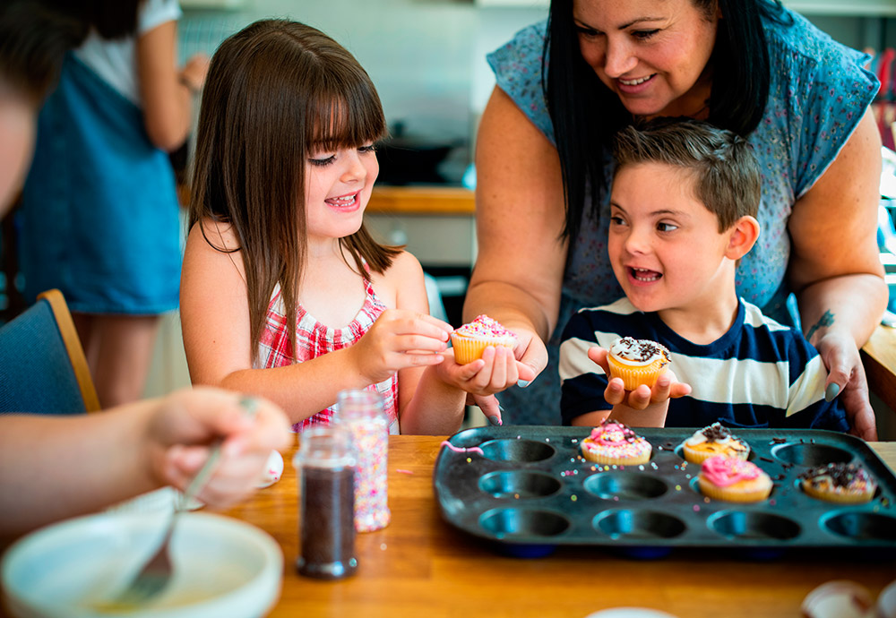 Un niño con síndrome de Down cocina unas cupcakes junto a su hermana y su madre.