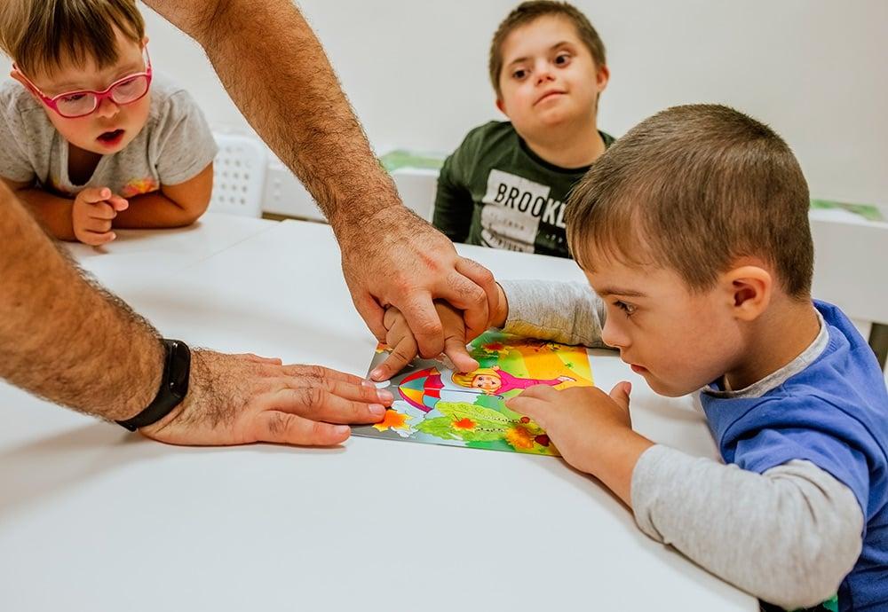 Un grupo de niños con síndrome de Down aprenden en un centro de terapia ocupacional.