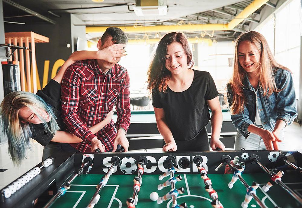 Trabajadores de una empresa se divierten jugando al futbolín durante una pausa en el trabajo.