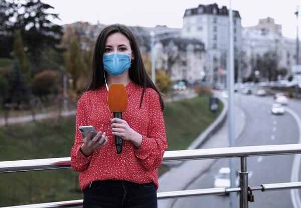 Periodista realiza un directo con mascarilla mientras sujeta un teléfono móvil sobre el puente de una avenida