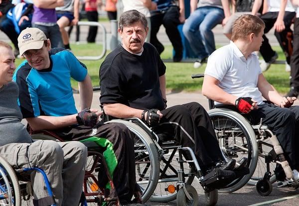 Cuatro adultos en silla de ruedas momentos antes de realizar una prueba deportiva.