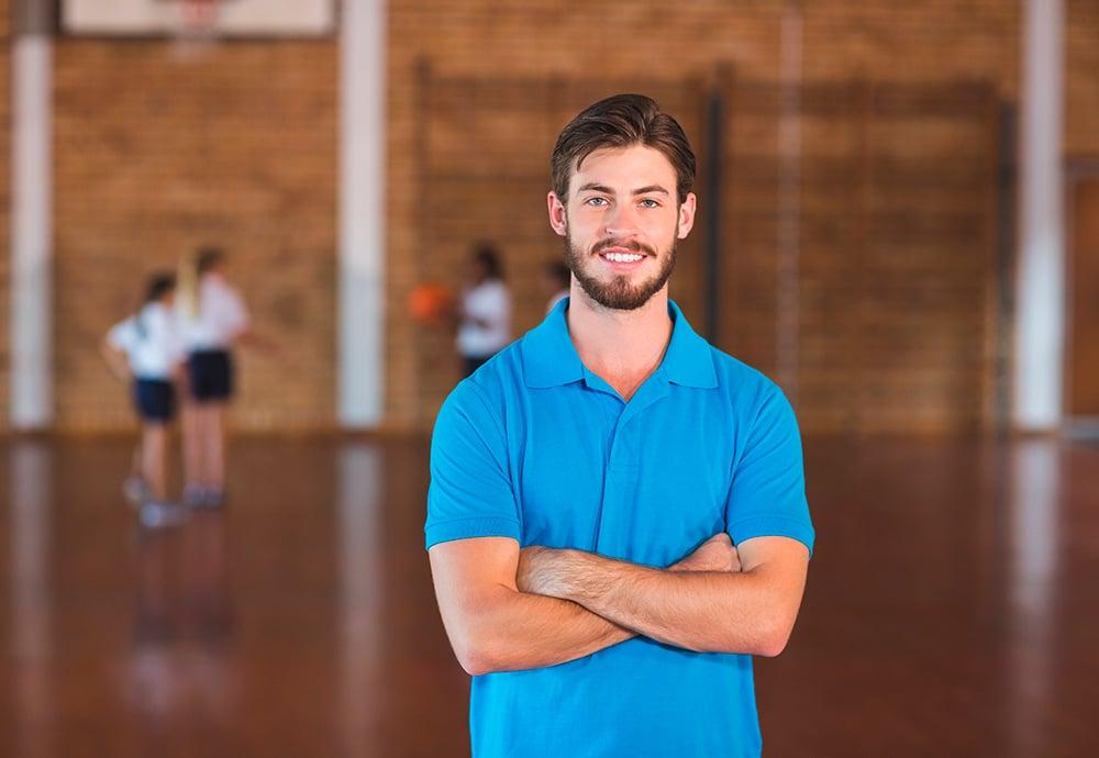 Profesor de Educación Física en un gimnasio escolar con brazos cruzados mirando a la cámara.
