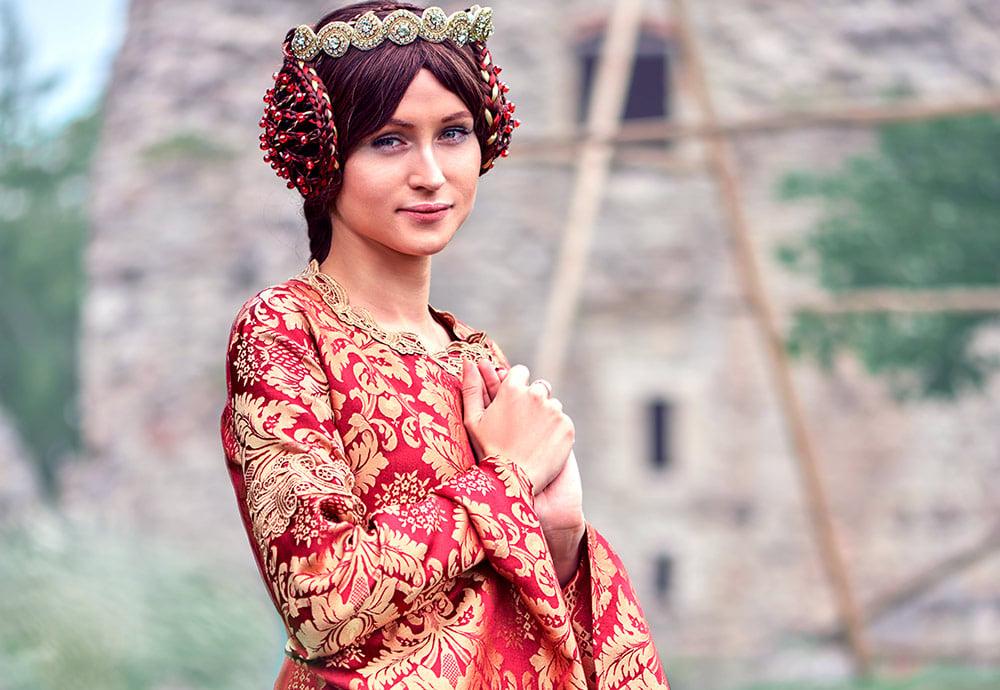 Isabel de Francia, reina de Inglaterra en el período de la Edad Media en vestido rojo delante de un castillo medieval.