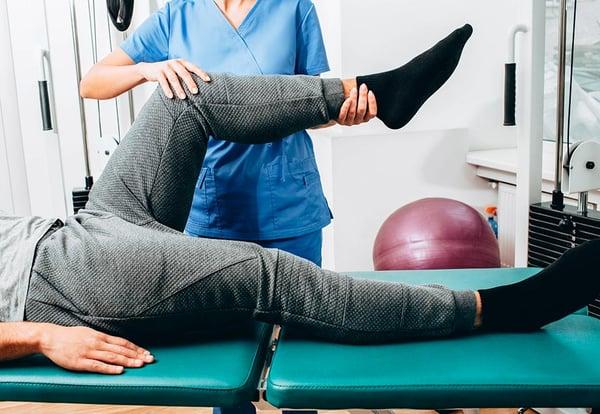 Una fisioterapeuta realiza estiramientos a un paciente acostado sobre una camilla