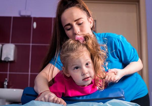 Una terapeuta ocupacional ayuda en la rehabilitación de una niña acostada con con parálisis