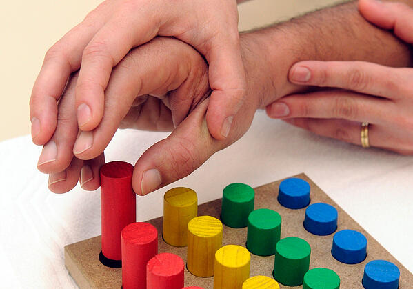 Detalle de la mano de un terapeuta sobre la de un paciente que realiza una terapia ayudado por unos palos de madera de colores
