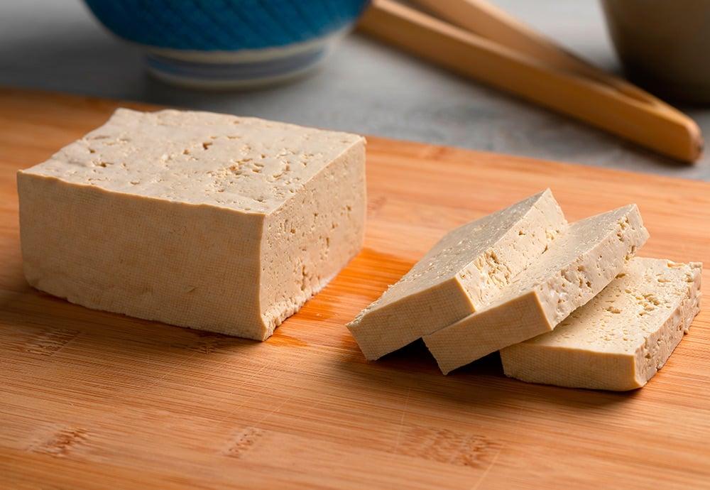 Pedazo de tofu fresco en rodajas sobre una tabla de cortar.