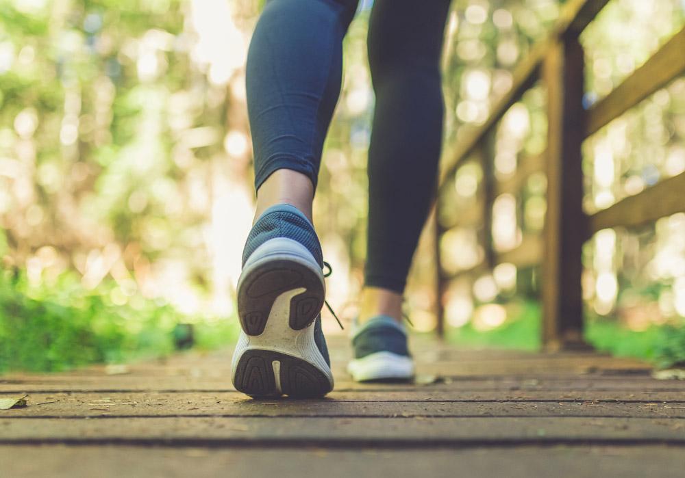 Piernas de una corredora cruza caminando una pasarela madera en medio de un bosque