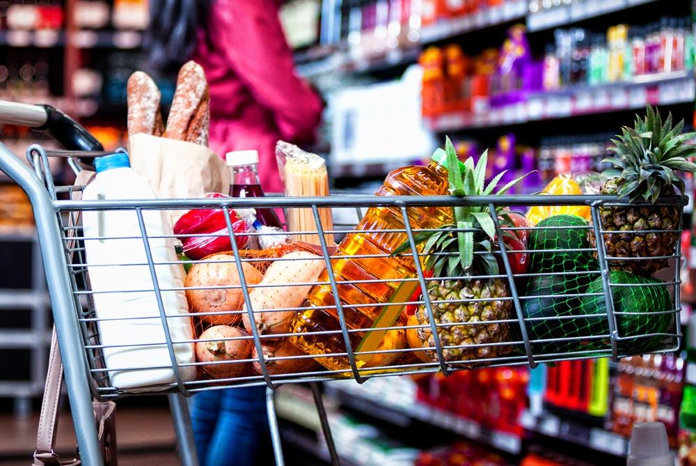 Carro de la compra con productos frescos: fruta, pan,aceite...