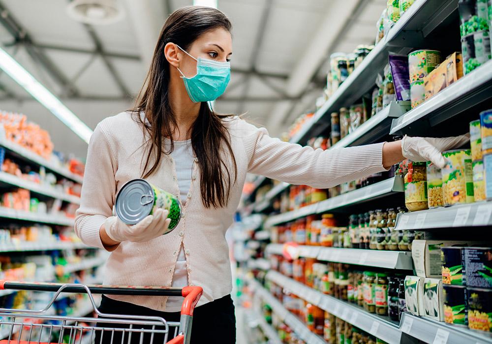 Una mujer joven con mascarilla realiza una compra en el supermercado durante el estado de alarma por coronavirus