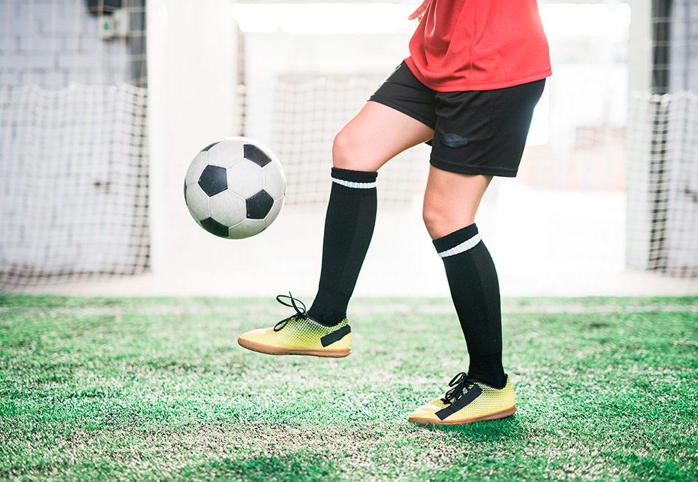 Medio cuerpo de una futbolista dando toques a un balón.