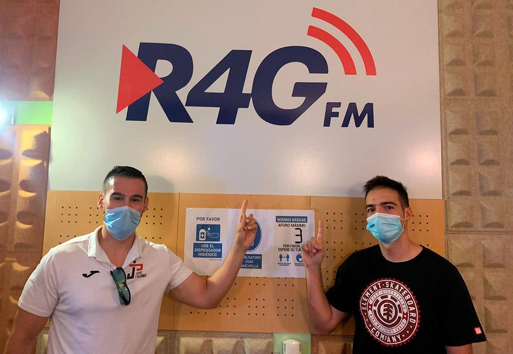 Gonzalo Torinos y Jaime Palomo en los estudios de Radio4G señalando hacia arriba al logotipo de la emisora